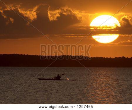 Kayaker Splashing At Sunset