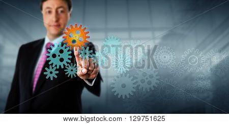 Happy businessman is touching a cog in a virtual gear train. The selected pinion icon is lighting up orange. Business metaphor for IT service management information services or process engineering.