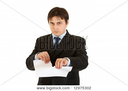 Displeased modern businessman tearing document isolated on white