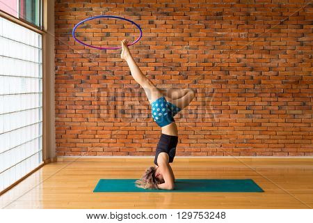 Woman dancing with a hula hoop in a beautiful studio while doing a headstand