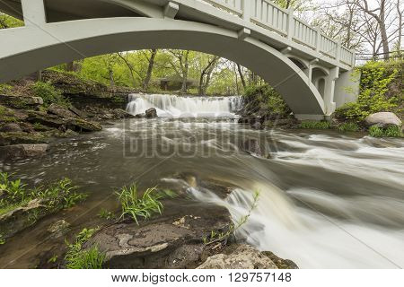 A waterfall with a footbridge during spring.