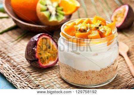 cheesecake in a jar with tropical fruits: mango passionfruit.  kiwi slices orange and passionfruit on straw background