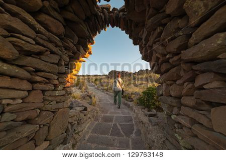 Tourist exploring Inca trails at sunset on Amantani' Island Titicaca Lake among the most scenic travel destination in Peru. Travel adventures and vacations in the Americas.