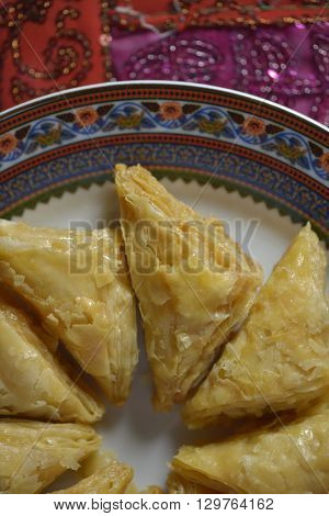 An oriental sweet dish - Baklava. a puffed pastries in a plate. Partial view from above.