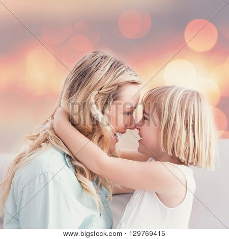 Mother and daughter rubbing noses on sofa against background of multiple color