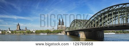 Panoramic view of the Cologne Cathedral with Hohenzollern Bridge and Rhine River in Germany the church Great St. Martin to the left