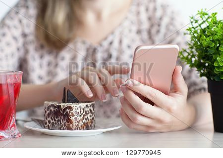 woman having breakfast in a cafe and holding a pink phone