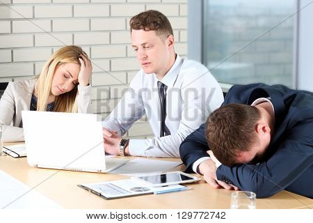 Boring work. Young business people looking bored while sitting together at the table and looking away
