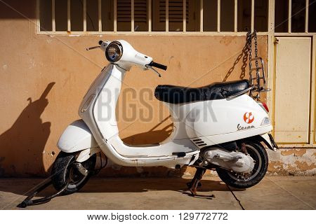 SANTA MARIA, CAPE VERDE - DECEMBER 16, 2015: Old white Vespa Scooter secured by the wall
