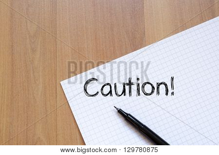 Caution text concept write on notebook .
