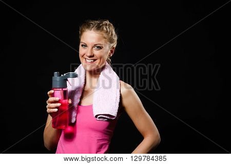 Beautiful blonde woman is drinking water after exercise.
