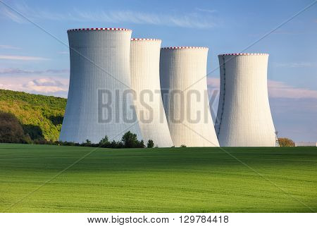 Nuclear power plant with  green field and blue sky.