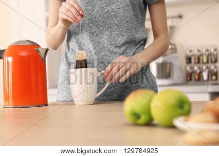 Woman making tea in the kitchen