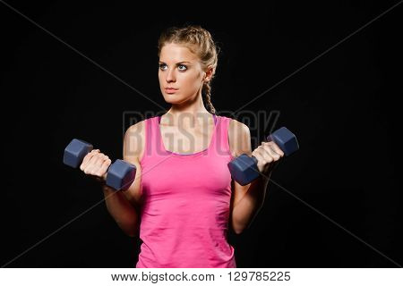 Beautiful young woman is exercising with dumbbells.