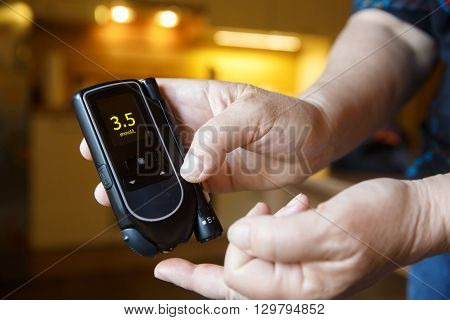 Hypoglycemic diabetic patient testing her blood for sugar level at home; low blood sugar. Medical process self-diagnose common metabolic widespread and modern epidemic disease concept.