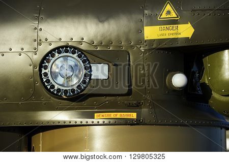 Headlight of military helicopter on armored side of green combat flying vehicle with rivets, air force, modern aviation and aerospace industry poster
