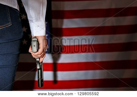 Woman holding handgun on USA national flag background