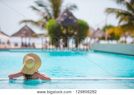 Young beautiful woman enjoying the luxurious quiet swimmingpool