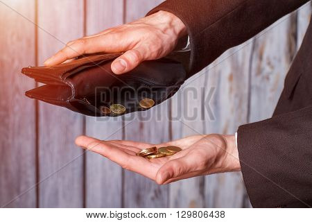 Hands holding coins and wallet. Black wallet and small coins. Not a cent more. The definition of poverty. poster
