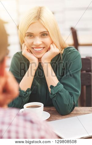Pretty young man and woman are talking and smiling in cafe. They are sitting at table and dinking coffee