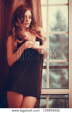 Sensual seductive woman in lingerie drinking cup of coffee by curtain and french door window at home. Young girl with hot energizing beverage stay awake. Caffeine energy.