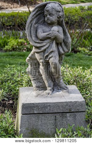A stone cherub set in a lush garden.