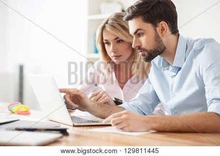 Talented creative team is discussing a project together. Man and woman are sitting at table in office. They are looking at laptop seriously