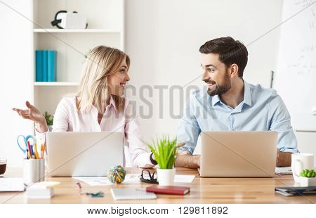 Friendly young colleagues are discussing a project with inspiration. They are sitting at desk near laptops and smiling. Man and woman are looking at each other with agreement