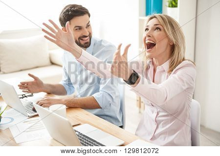 Cheerful creative team is celebrating their success. Woman is smiling and gesturing happily. Man is sitting at desk near laptop and looking at lady with joy