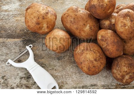 Single white plastic and metal peeler next to piles of raw yellow potatoes on top of old wooden table