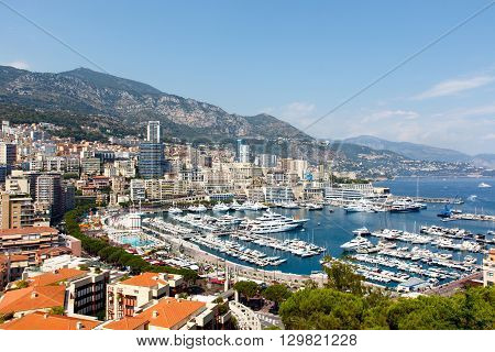 Monte Carlo harbor with luxury yachts and the city in the foreground