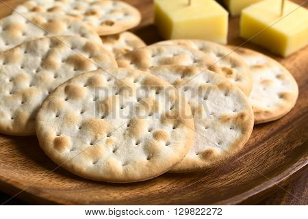 Saltine or soda crackers with cheese pieces on wooden plate photographed with natural ight (Selective Focus Focus in the middle of the first cracker)