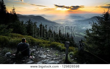 Man sitting and looking to nice sunset on czech mountains Beskydy