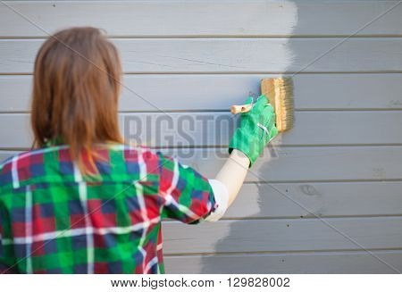 Woman applying protective varnish or paint on wooden house tongue and groove cladding elevation wall. House improvement  diy concept.