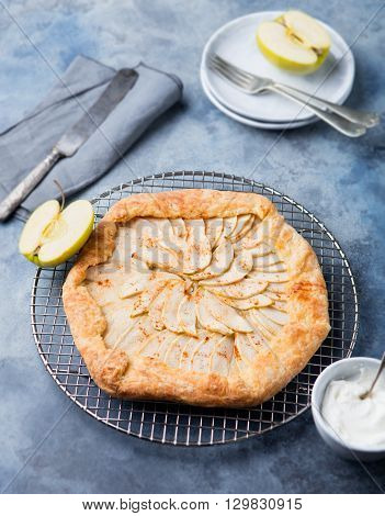 Apple galette, pie, tart with cinnamon on cooling rack on a blue stone background.