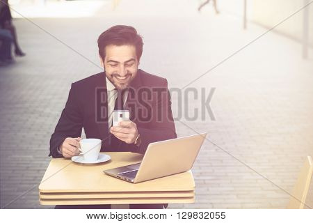 Toned picture of happy businessman using mobile phone and drinking coffee or tea in restaurant or cafe. Freelance man working on his laptop computer.