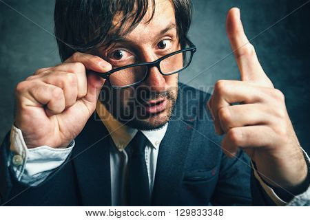 Angry tax inspector looking serious and determined aggressive finger threatening adult businessperson with glasses
