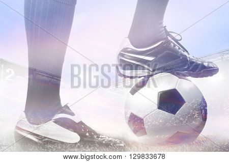 double exposure photo of stadium and legs of a soccer or football player on ball