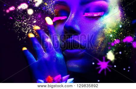 Fashion model woman in neon light, portrait of beautiful model with fluorescent make-up, Art design of female disco dancers posing in UV, colorful make up. Isolated on black background