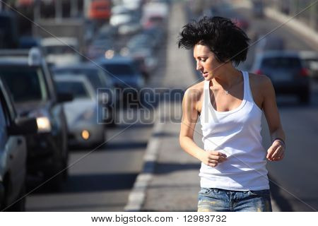girl runs on highway middle in city, view on belt