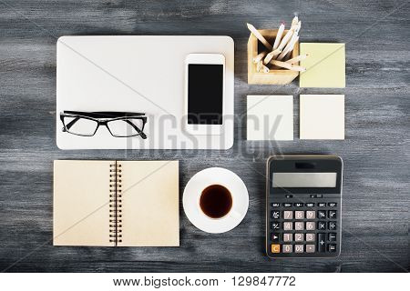 Dark wooden desktop with neatly organized laptop coffee cup notepad blank smart phone glasses calculator and other items. Top view Mock up