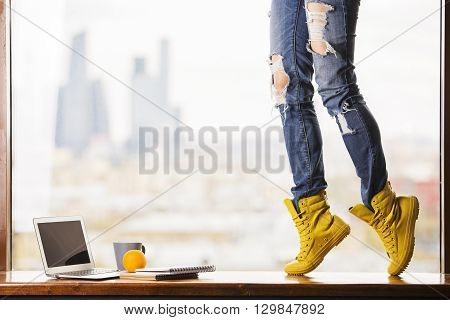 Girl's legs in yellow boots standing on windowsill with blank laptop screen orange coffee cup and notepads on blurry city background. Mock up