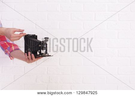 Man's hands with retro camera on blank brick wall background. Mock up