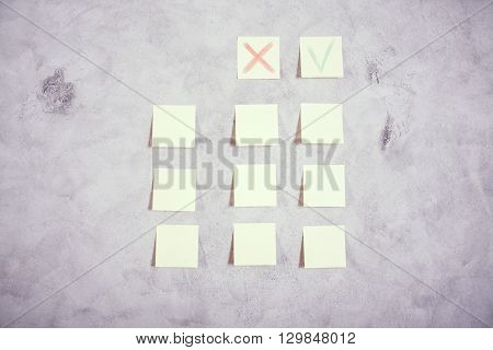 Paper stickers with cross and green tick glued onto grey concrete wall