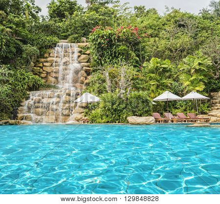 Paradise for tourists with crystal clear swimming pool, deckchairs with sunshades, beautiful waterfall and tropical forest.