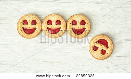 Four round biscuits smiling faces one of them falls down. Humorous food. Symbolic scene. Successes and failures.