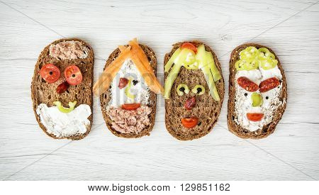 Four funny faces made of bread butter tuna sausage carrot paprika tomato and black pepper. Humorous food. Smiling faces. Creative food. Facial expression.