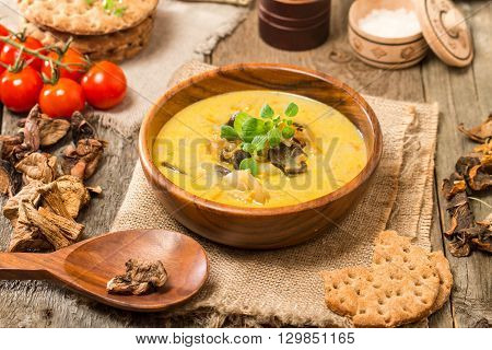 Cream of mushroom soup. Home-made, country style with dried mushrooms on wooden background