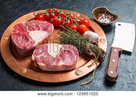 Raw veal shank slices meat and ingredients for Osso Buco cooking on black background, top view