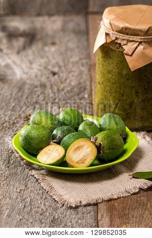 Fresh fruits of feijoa in abowl and feijoa jam on wooden table